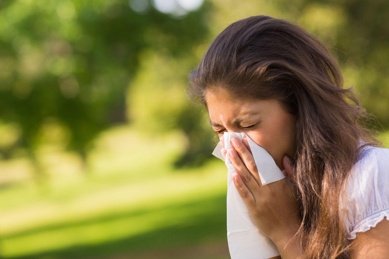 Eine junge Frau niest in ihr Taschentuch. Thema: Allergien