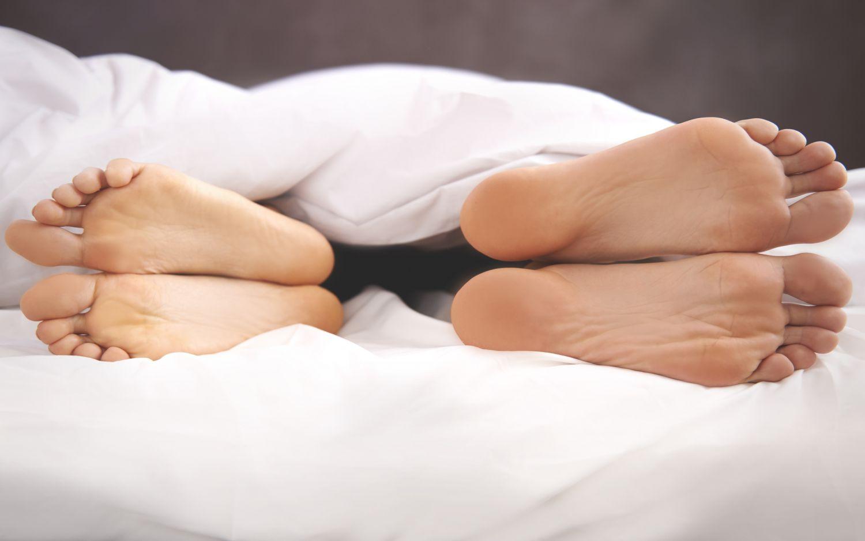 Zwei Fußpaare, die unter der Bettdecke hervorschauen. Thema: Schlafprobleme