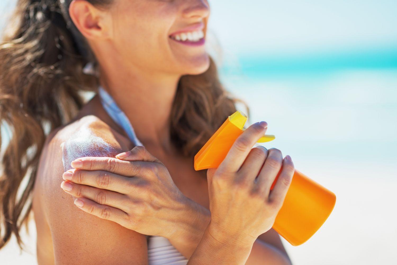 Eine Frau mit Sonnencreme in der Hand