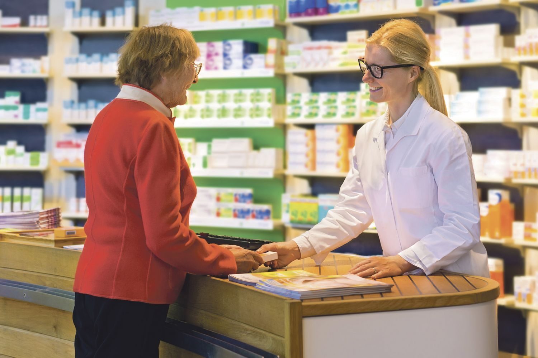 Kundin kauft ein Medikament in der Apotheke