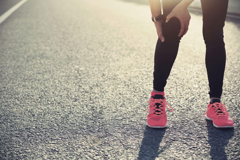 Läuferin hält sich das Knie. Thema: Gelenkschmerzen