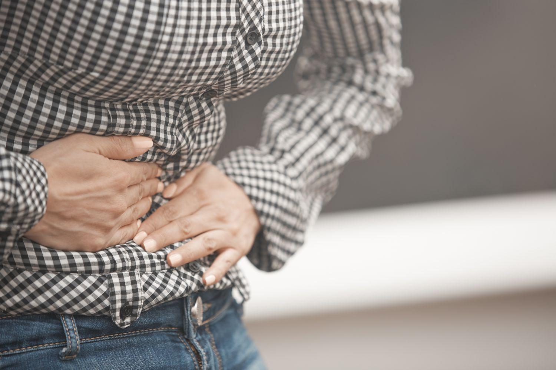 Eine Person hält sich den Bauch vor Schmerzen. Thema: Magen-Darm-Beschwerden