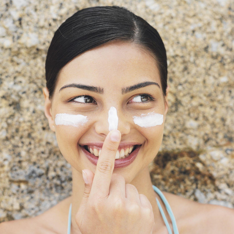 Frau mit Sonnencreme im Gesicht