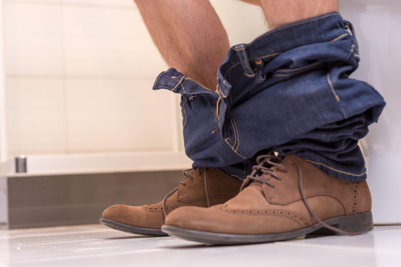 Eine Person sitzt mit heruntergelassener Hose auf Toilette. Thema: CED