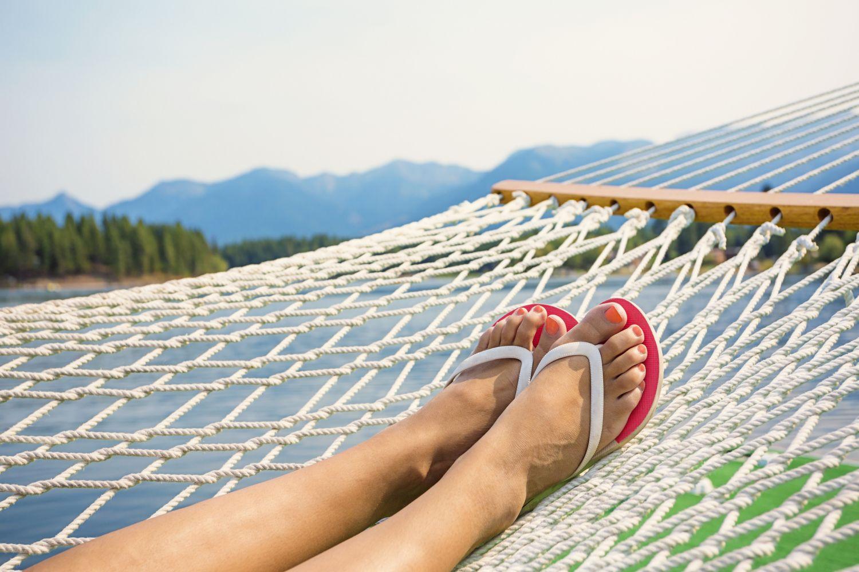 Füße in Flip-Flops auf einer Hängematte